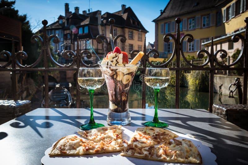 Traditionelle lokale Pizza mit Wein und Nachtisch in einem Café draußen lizenzfreie stockbilder
