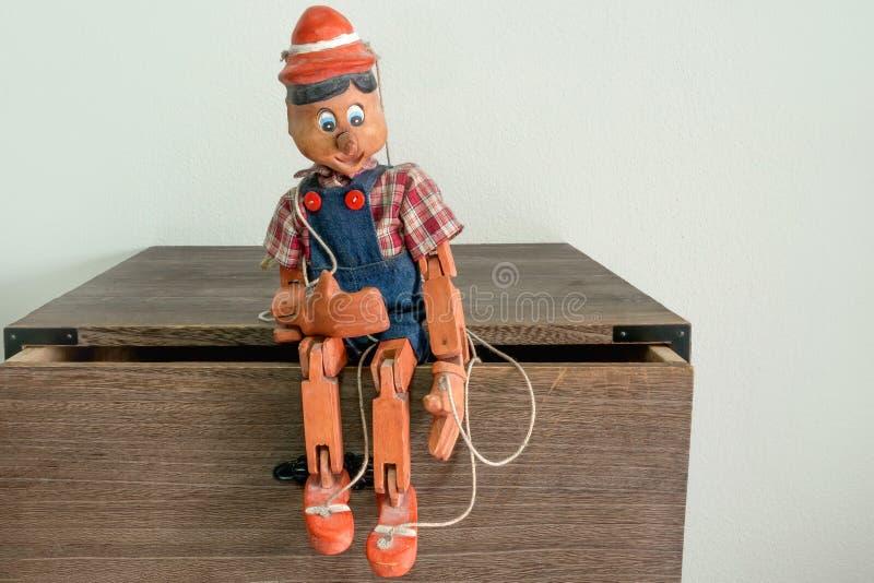 Traditionelle Marionetten gemacht vom Holz Sitzen Sie auf einem Kiefernholzkabinett stockfotografie