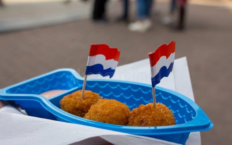 Traditionelle niederländische Straßennahrung verziert mit Holland-Flaggen Gebratene Fischbälle in der Platte mit Servietten und D stockbild