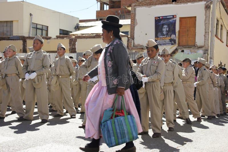 Traditionelle peruanische Frau, die durch eine Gruppe Schulkinder überschreitet lizenzfreie stockfotografie