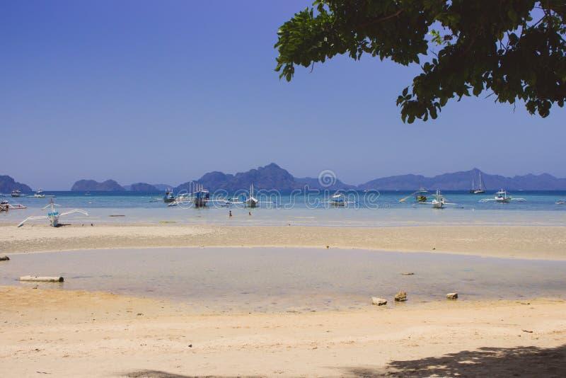 Traditionelle Philippinen-Boote auf Seeküste in EL Nido Szenische tropische Landschaft mit Inseln und Bergen auf Horizont lizenzfreie stockfotos