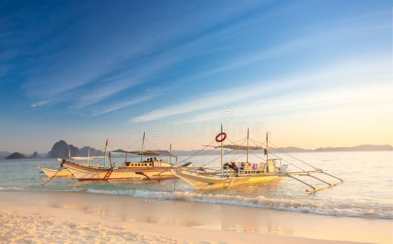 Traditionelle philippinische Boote auf weißem sandigem Strand bei Sonnenuntergang im Hafen Barton, Palawan-Insel, Philippinen stockfotografie