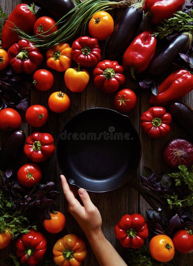 Traditionelle Roheisen-Bratpfannewanne auf Weinleseholztisch mit sortiertem Gemüsehintergrund Messer und Gabel stockfotografie
