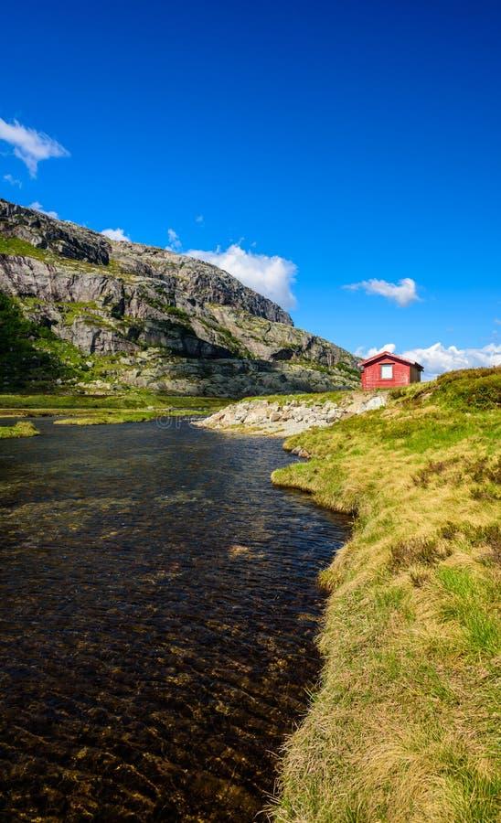 Traditionelle schöne norwegische rote Kabine auf einem Seeufer lizenzfreie stockfotografie