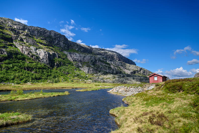 Traditionelle schöne norwegische rote Kabine auf einem Seeufer lizenzfreie stockfotos