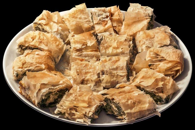 Traditionelle serbische Spinats-Käse-Rollentorte angeboten geschnitten auf runder Porzellan-Servierplatte auf schwarzem Hintergru stockfoto