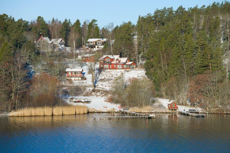 Traditionelle skandinavische ländliche Häuser auf dem Ufer von einem Fjord, März-Tag schweden lizenzfreie stockfotografie
