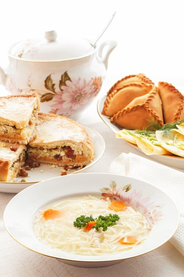 Traditionelle tatarische Feiertagstabelle Tokmach - Nudelsuppe mit Huhn Dreiecke - Fleischtorten und süßer Kuchen lizenzfreie stockbilder