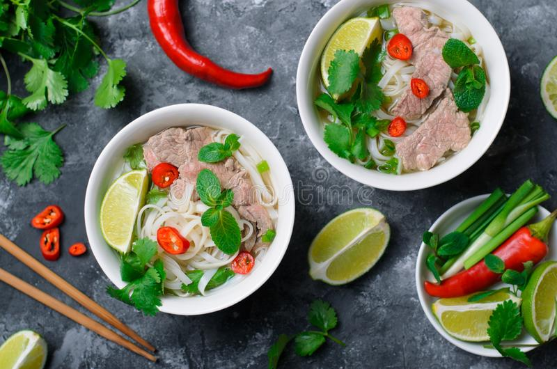 Traditionelle vietnamesische Suppe Pho BO mit Reis-Nudeln, Rindfleisch und Kräutern auf dunklem Hintergrund lizenzfreies stockfoto