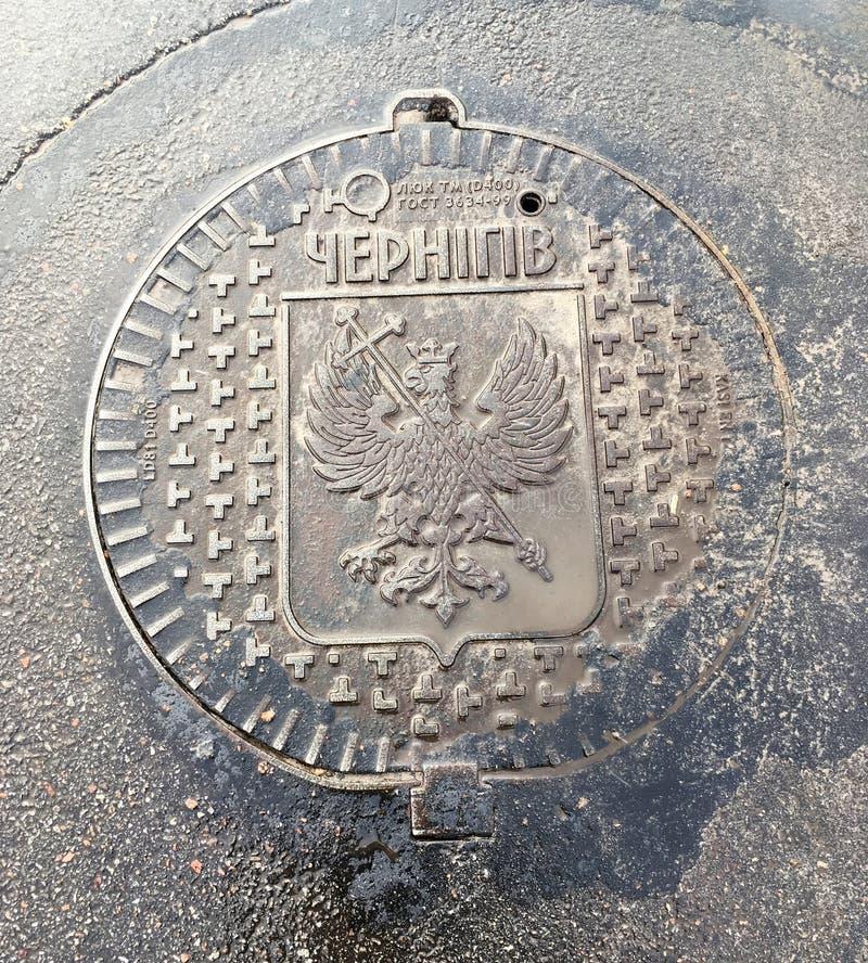 Traditioneller Chernihiv-Kanaldeckel oder Abflussdeckel mit dem Hauptadlersymbol der Stadt zwei stockfoto