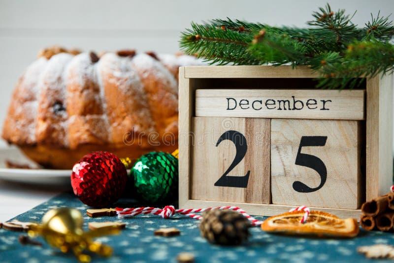 Traditioneller Fruchtkuchen für Weihnachten verziert mit Puderzucker und Nüssen, Rosinen nahe bei hölzernem Kalender mit Datum am lizenzfreie stockfotos