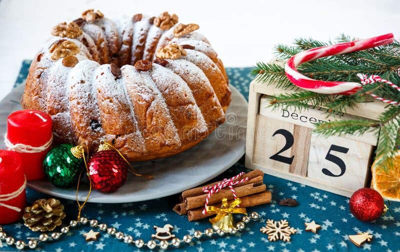 Traditioneller Fruchtkuchen für Weihnachten verziert mit Puderzucker und Nüssen, Rosinen nahe bei hölzernem Kalender mit Datum am stockfotografie