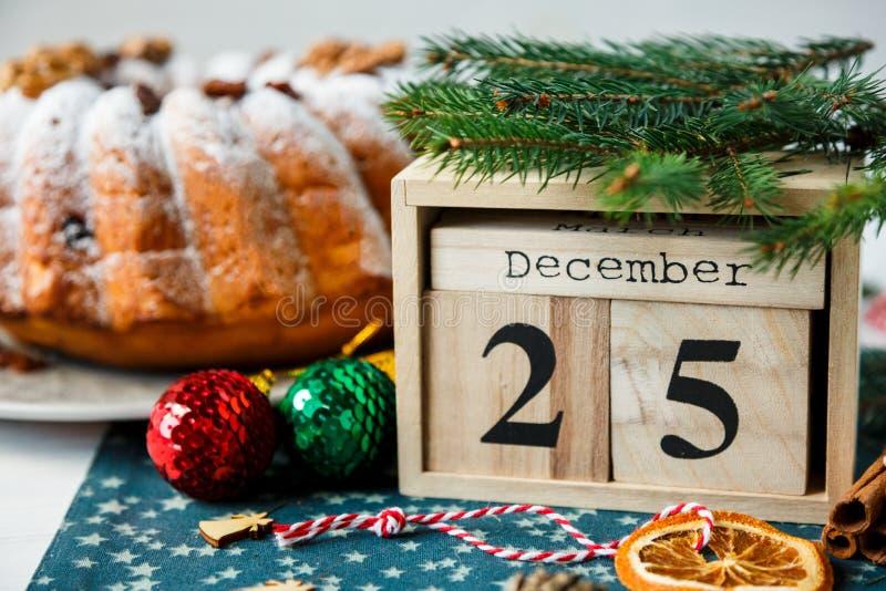 Traditioneller Fruchtkuchen für Weihnachten verziert mit Puderzucker und Nüssen, Rosinen nahe bei hölzernem Kalender mit Datum am stockbilder