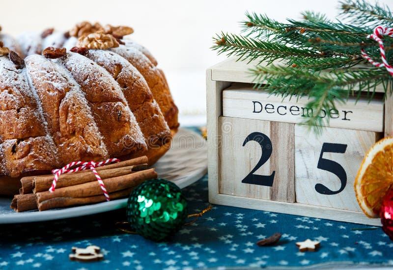 Traditioneller Fruchtkuchen für Weihnachten verziert mit Puderzucker und Nüssen, Rosinen nahe bei hölzernem Kalender mit Datum am lizenzfreies stockfoto