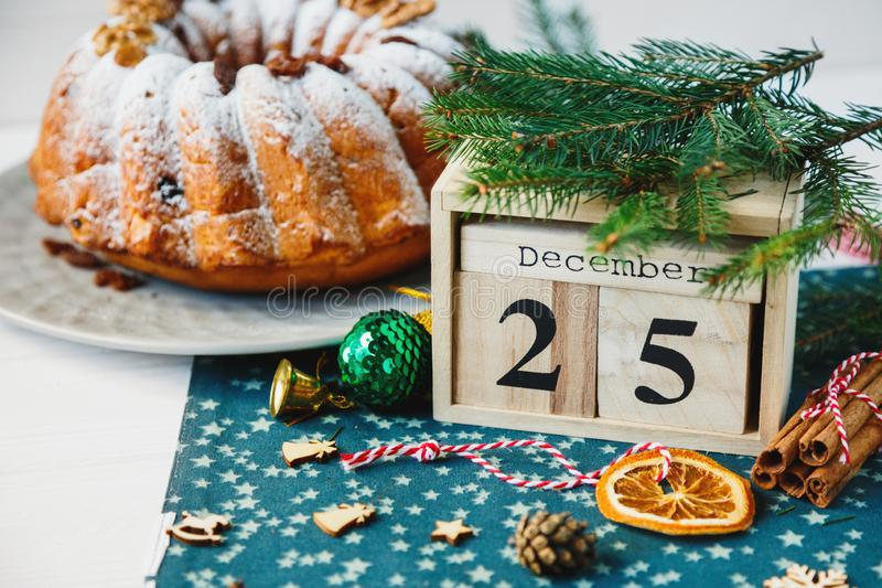 Traditioneller Fruchtkuchen für Weihnachten verziert mit Puderzucker und Nüssen, Rosinen nahe bei hölzernem Kalender mit Datum am lizenzfreies stockbild
