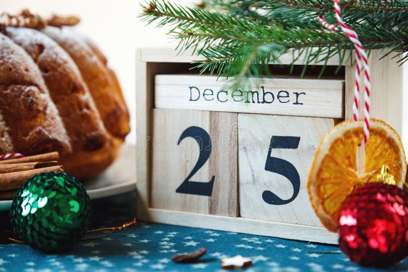 Traditioneller Fruchtkuchen für Weihnachten verziert mit Puderzucker und Nüssen, Rosinen nahe bei hölzernem Kalender mit Datum am stockfoto