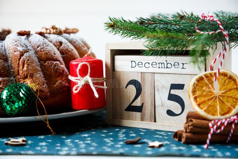 Traditioneller Fruchtkuchen für Weihnachten verziert mit Puderzucker und Nüssen, Rosinen nahe bei hölzernem Kalender mit Datum am stockbild