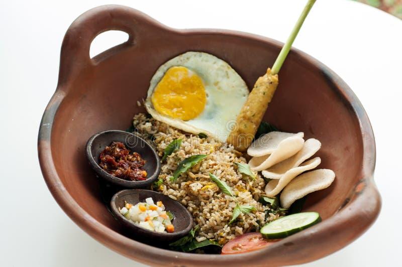 Traditioneller gebratener Reis mit satay kühler Soße, Tomate und Essiggurke lizenzfreie stockfotografie