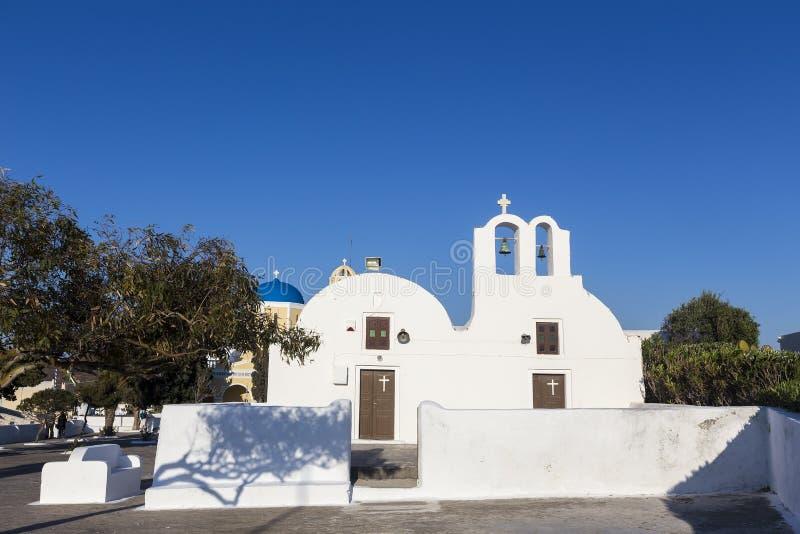 Traditioneller griechischer weißer Kirchenbogen mit Kreuz und Glocken im vill stockbild