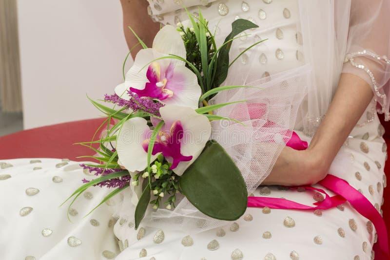 Traditioneller Hochzeitsbrautabschluß herauf die Hände, die Blumen halten stockfoto
