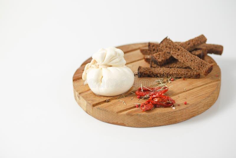 Traditioneller italienischer Käse Burrata auf einem hölzernen Brett mit Gewürzen und sonnengetrockneten Tomaten stockbilder