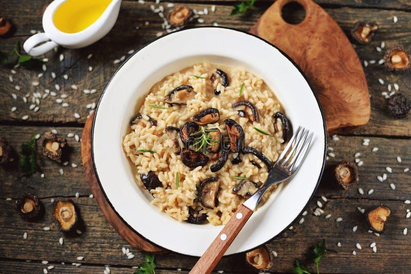 Traditioneller italienischer Risotto mit getrockneten Pilzen, Parmesankäseparmesankäse, Gemüsesuppe und Weißwein stockfotografie
