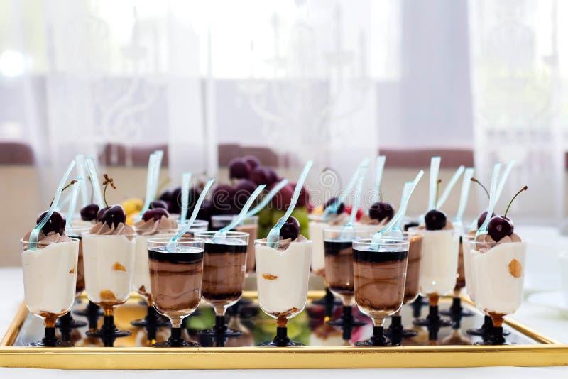 Traditioneller italienischer Tiramisunachtisch mit Schokoladensoße in einem Glas auf einem widergespiegelten Behälter stockfotos
