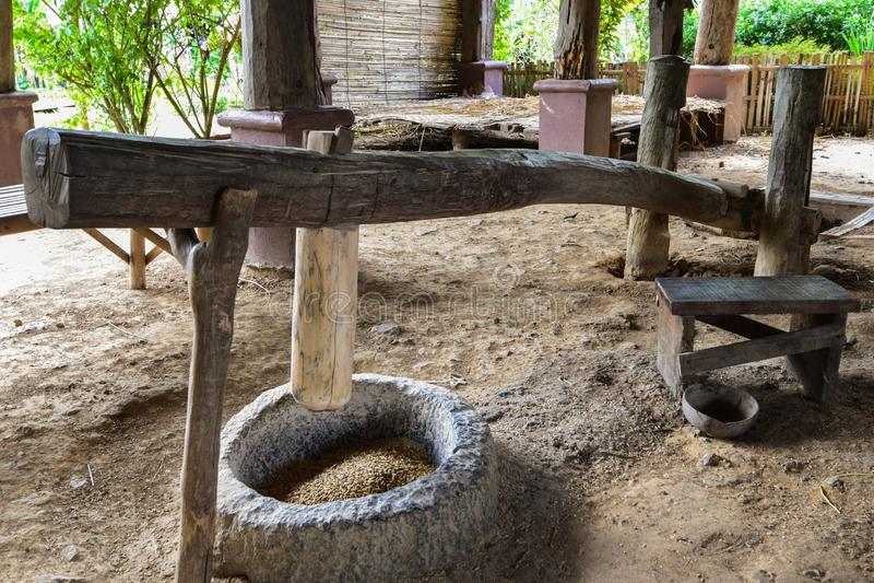 Traditioneller Reis, der mit einem hölzernen Mörser und einer Stampfe, hölzerne handgemachte Kultur des Reismörsers, traditionell lizenzfreies stockbild