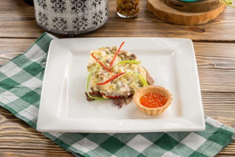 Traditioneller russischer Salat Olivier mit rotem Kaviar auf quadratischer Platte auf Holztisch stockfotos