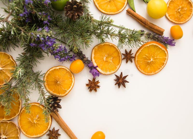 Traditioneller rustikaler Weihnachtshintergrund mit Mittelmeerthema: Zimtstangen, Kiefernkegel, Sternanis, trockene Orangen, blüh stockfotos