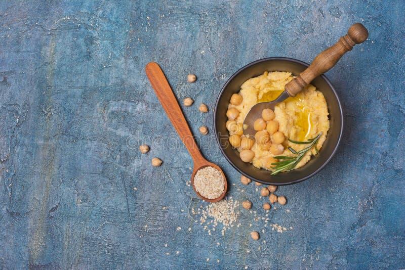 Traditioneller selbst gemachter Kichererbse hummus Imbiss mit Gewürz von Rosmarin- und Sesamsamen im hölzernen Löffel lizenzfreie stockfotos