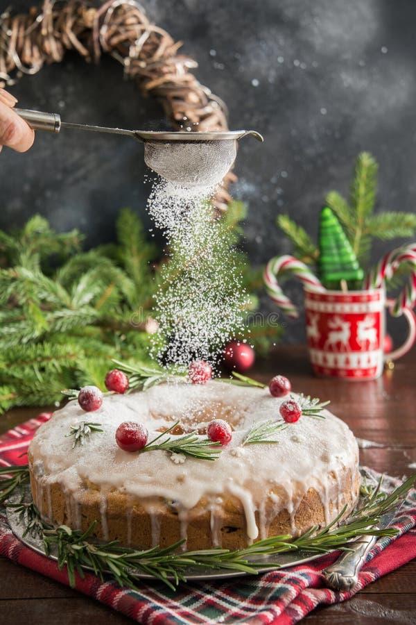 Traditioneller selbst gemachter Weihnachtskuchen mit Garnierungsmoosbeere und -rosmarin auf dekorativer Platte Pulverisierung mit lizenzfreie stockfotografie