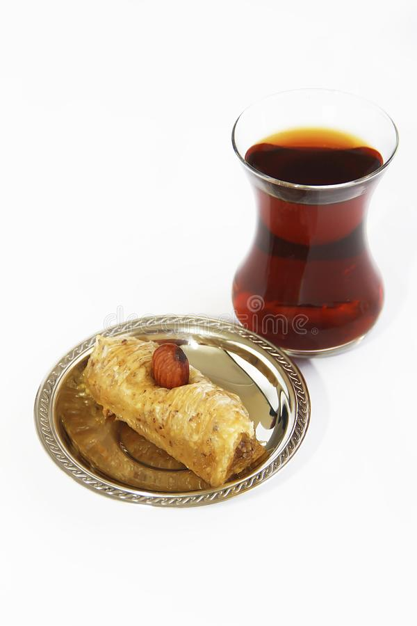 Traditioneller türkischer Bonbon mit Baklavanüssen und türkischer Tee in einem Glasbecher lizenzfreie stockbilder
