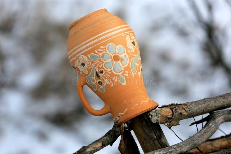 Traditioneller ukrainischer Lehmkrug auf einem Bretterzaun im Dorf stockbilder