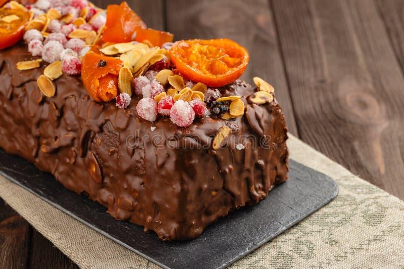 Traditioneller Weihnachtsfruchtkuchen in der Schokoladenglasur auf hölzernem Ba lizenzfreies stockfoto