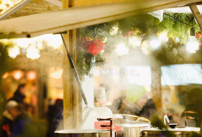 Traditioneller Weihnachtsstall am Markt des neuen Jahres und des Weihnachten mit Lichtern, Dekorationen, Bottiche mit heißen Tees lizenzfreies stockbild