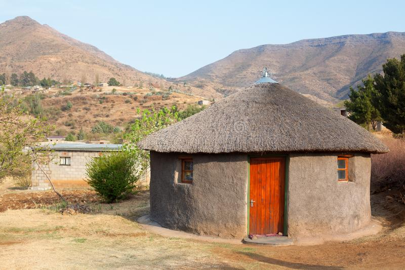 Traditionelles afrikanisches rundes Lehmhaus mit Strohdach im Dorf, Königreich Lesotho, südlicher Afrika, ethnisches Basothohaus stockfotografie