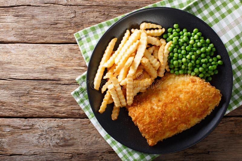 Traditionelles britisches Lebensmittel: Fisch und mit Abschluss-u der grünen Erbsen lizenzfreies stockbild