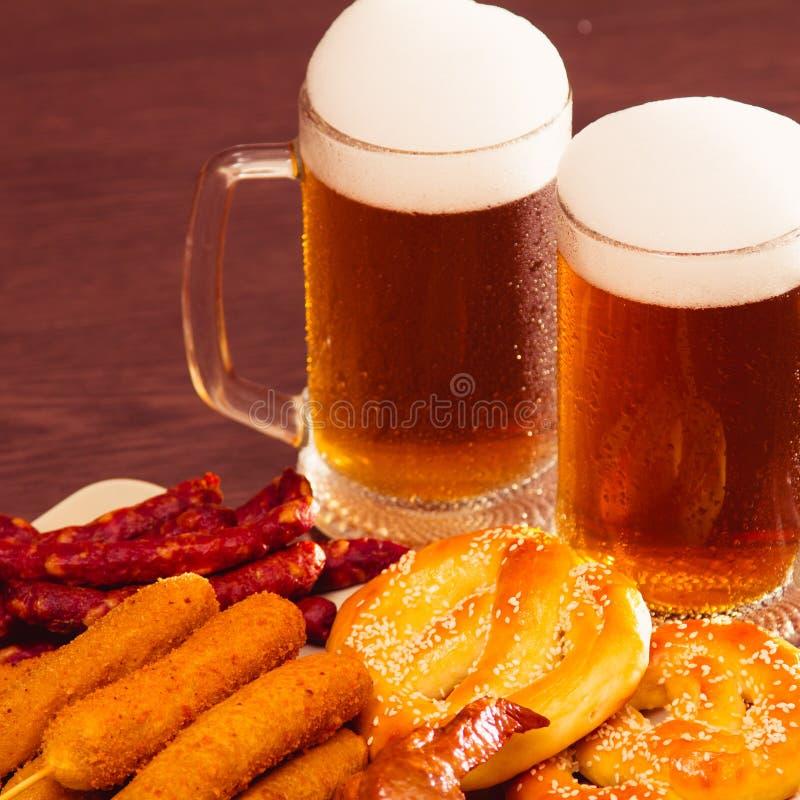 Traditionelles deutsches Lebensmittel Oktoberfest-Bier, gebackene Hühnerflügel, Popcorn, Zusammenstellung von verschiedene Würste lizenzfreie stockbilder