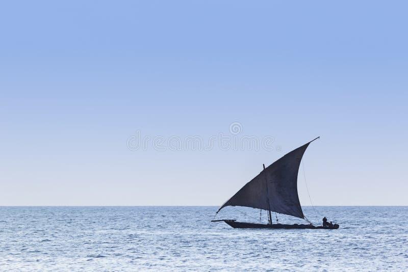 Traditionelles Dhowsegelschiff benutzt, um die Leutewaren und -waren zu transportieren silhouettiert gegen ein blaues coean und e lizenzfreie stockfotos