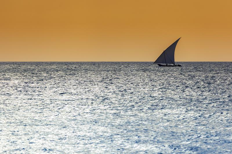 Traditionelles Dhowsegelschiff benutzt, um die Leutewaren und -waren zu transportieren silhouettiert gegen einen warmen Himmel un lizenzfreies stockfoto