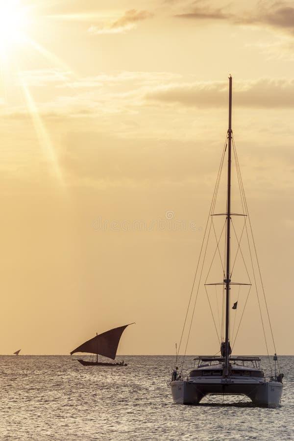 Traditionelles Dhowsegelschiff benutzt, um Leutewaren und -waren gegen ein modernes Katamaran zu transportieren lizenzfreie stockfotografie