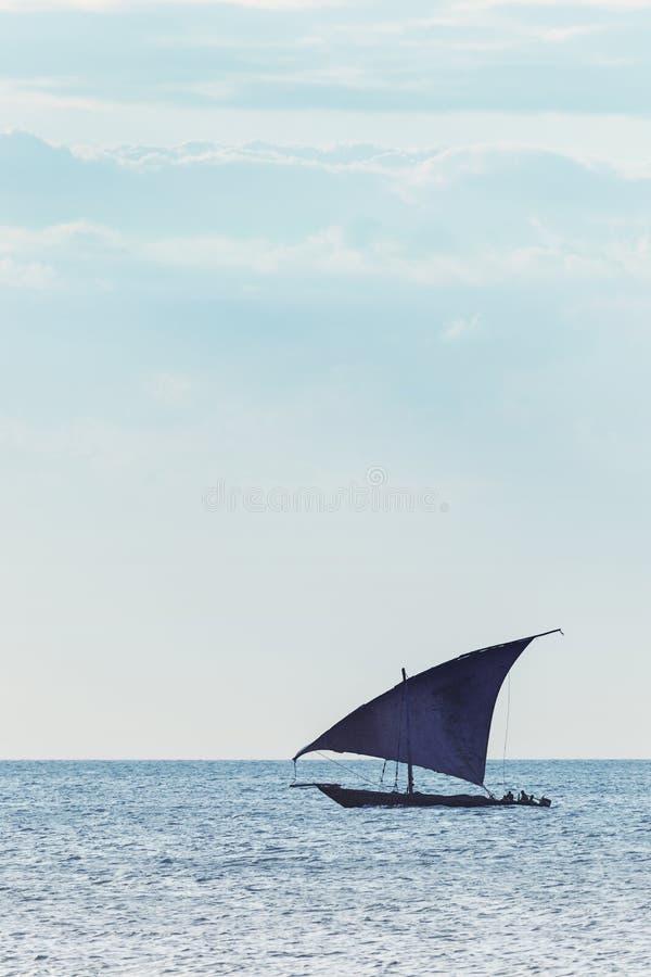 Traditionelles Dhowsegelschiff benutzt, um Leutewaren und -waren gegen einen entfernten Ozeanhorizont zu transportieren stockfotografie