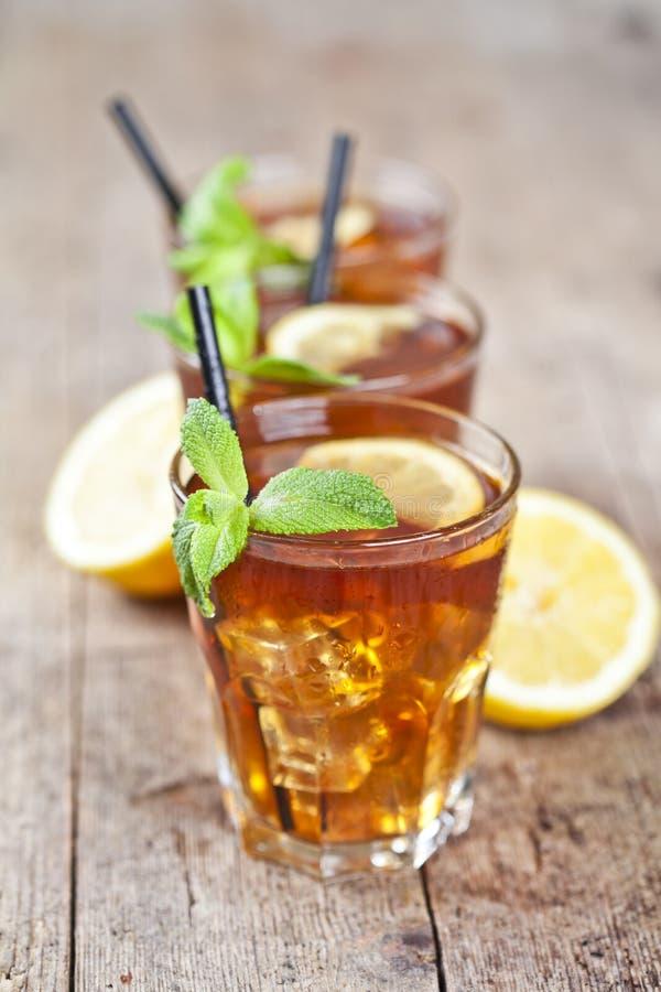 Traditionelles Eistee mit Zitrone, tadellosen Blättern und Eiswürfeln in drei Gläsern auf rustikalem Holztisch lizenzfreies stockfoto
