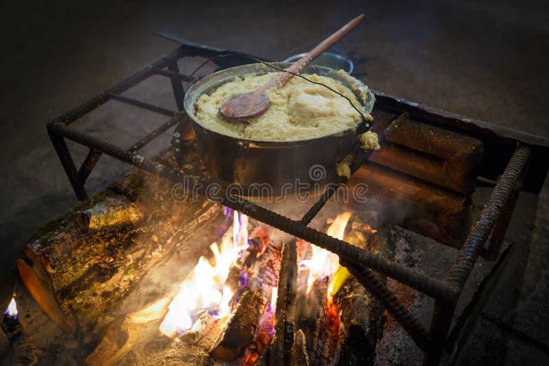 Traditionelles georgisches Lebensmittel, Maisbrei mamaliga wird im Großen kochenden Topf auf Feuer gekocht stockfotos