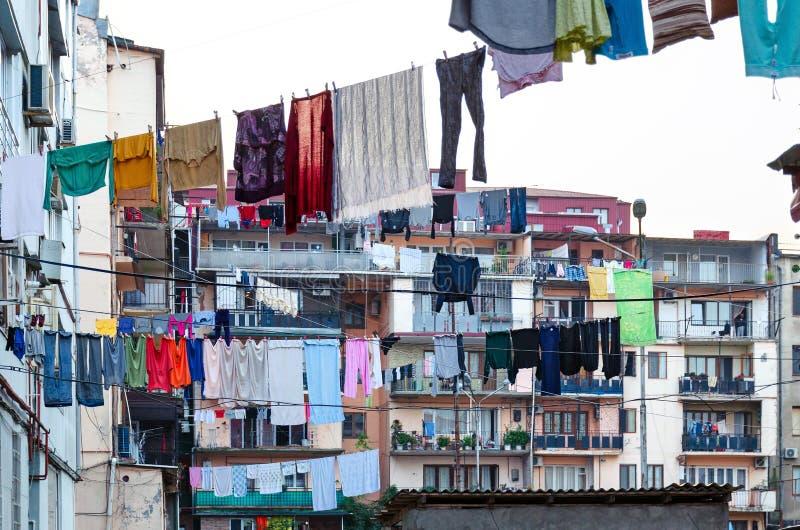 Traditionelles georgisches Yard - gewaschene Kleidung wird an Seile unter hohen Gebäuden gehangen stockfotografie