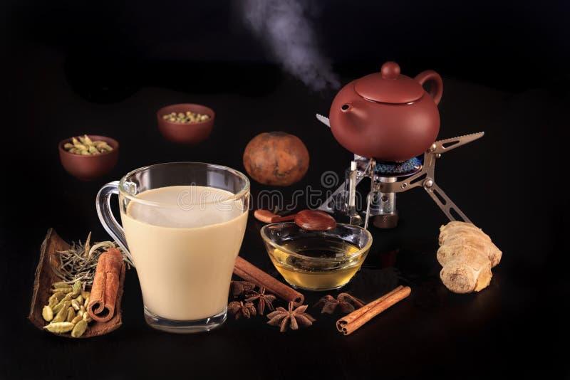 Traditionelles indisches Tee masala mit Gewürzen und einer Teekanne mit Dampf auf Feuer für das Schweißen stockfotos
