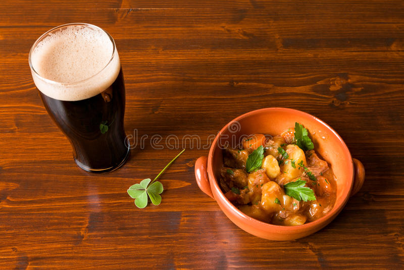 Traditionelles irisches Eintopfgericht mit einem halben Liter des stout Bieres und des Shamrocks stockbild