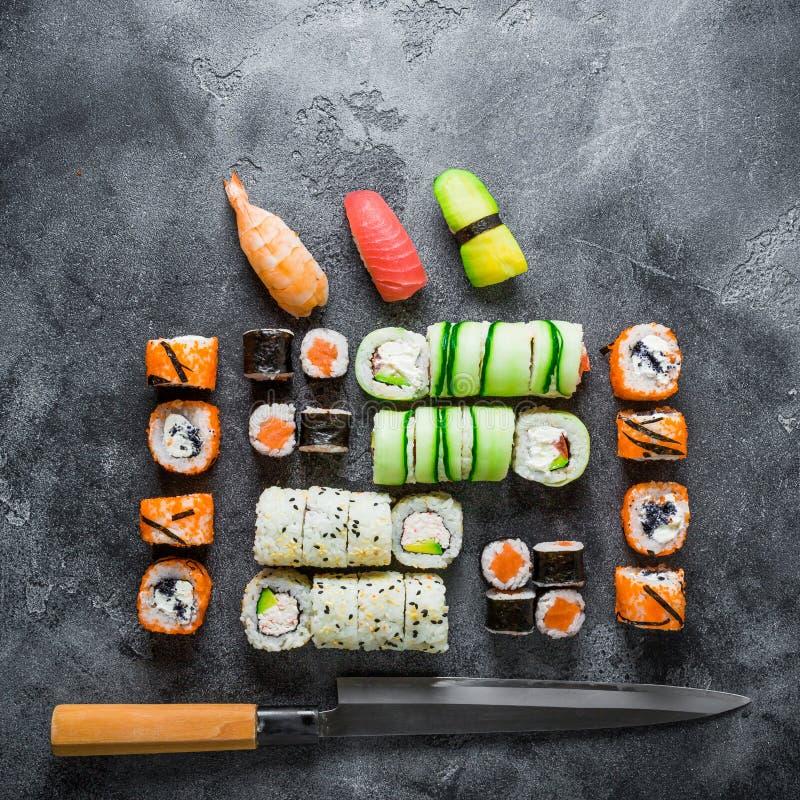 Traditionelles japanisches Lebensmittel von Sushi, von Rollen und von Messer auf grauem Hintergrund Flache Lage, Draufsicht lizenzfreies stockfoto