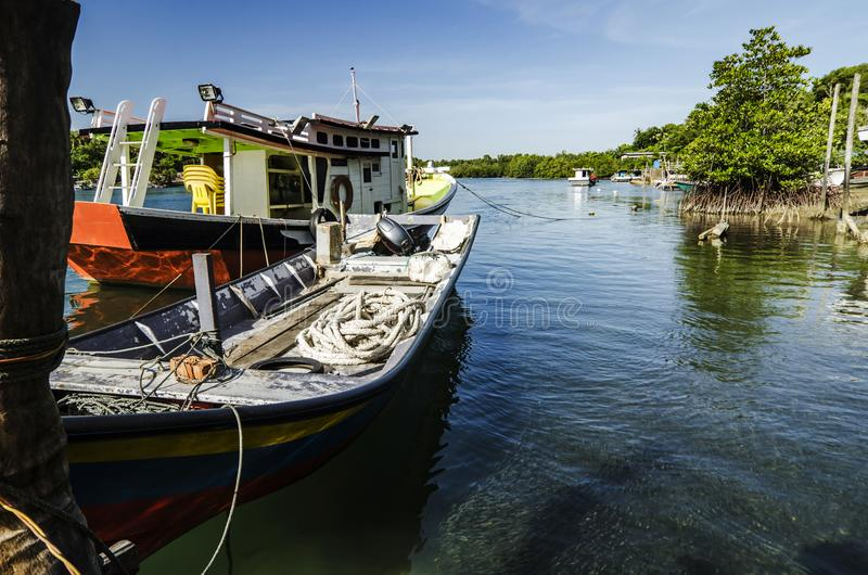 traditionelles malaysisches Fischerboot machte, hölzerne Anlegestelle und blauer Himmel fest stockbilder